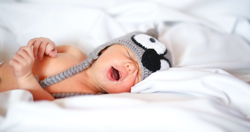 Beba sa kapom zeva na krevetu