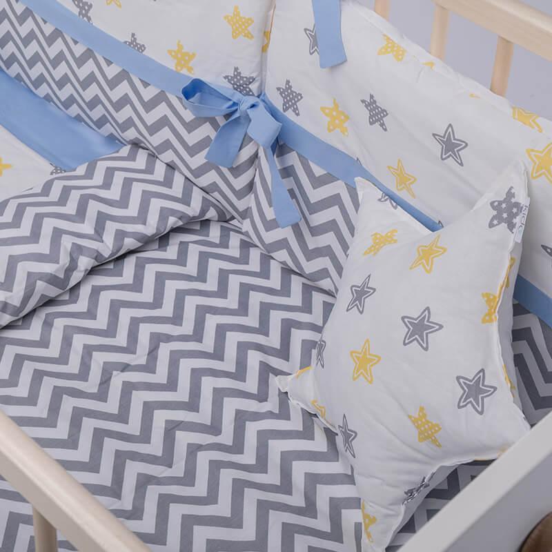 Kido jastuk u obliku zvezde bele boje sa šarenim zvezdicama