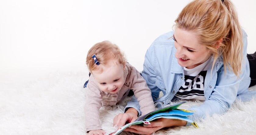 Mama pokazuje bebi ilustracije iz knjige