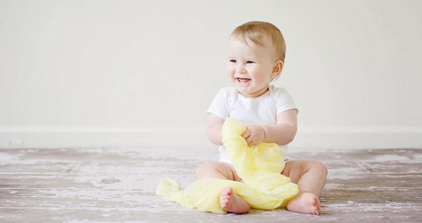 Beba koja sedi na podu i smeje se