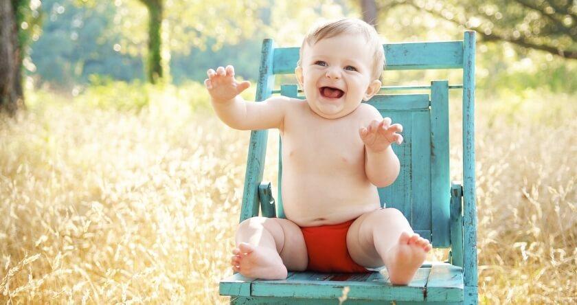Beba u crvenoj peleni sedi na stolici napolju