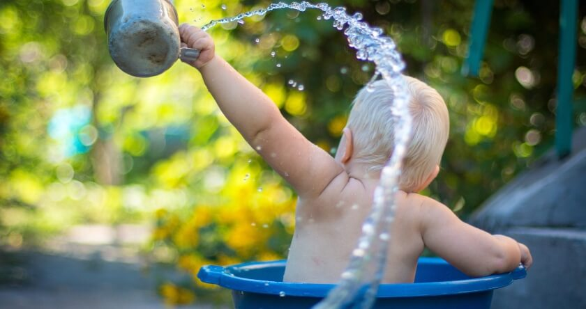 Beba koja se kupa u plavom koritu