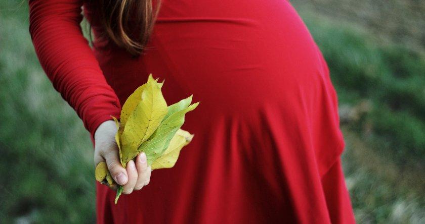 Trudnica u crvenoj haljini drži lišće u ruci