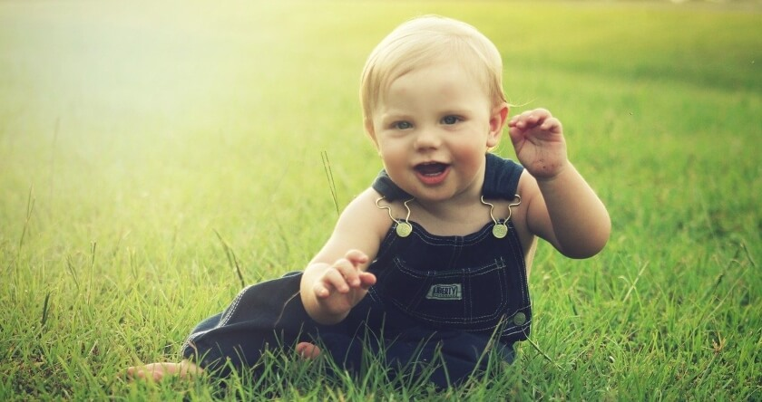 Plavokosa beba na zelenoj travi