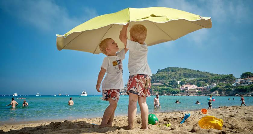 Dva dečaka ispod žutog suncobrana na plaži